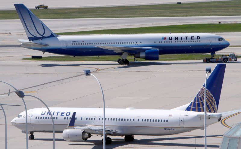 FILE PHOTO: A United Airlines plane with the Continental Airlines logo on its tail, taxis to the runway while another United plane heads for the gate at O'Hare International airport in Chicago