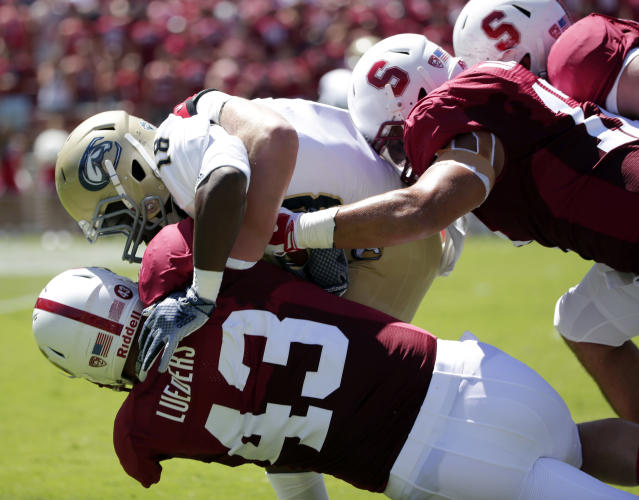 UC Davis wide receiver Jermale Jefferson, center, is brought down by three Stanford defenders during the first half of an NCAA college football game on Saturday, Aug. 30, 2014, in Stanford , Calif. (AP Photo/Marcio Jose Sanchez)