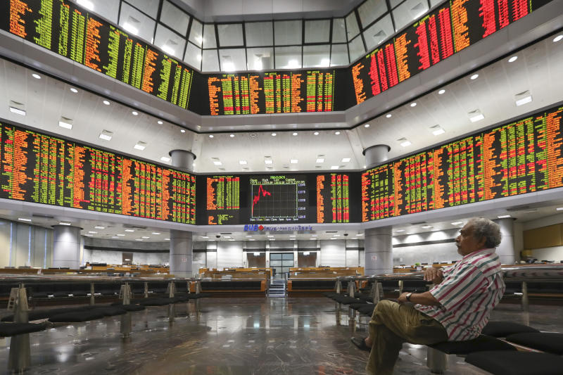 Visitor watch a stock trading board at a private stock market gallery in Kuala Lumpur, Malaysia, Friday, Jan. 11, 2019. Asian markets were mostly higher on Friday as investors cheered a more reactive Federal Reserve and U.S.-China trade talks. (AP Photo/Vincent Thian)