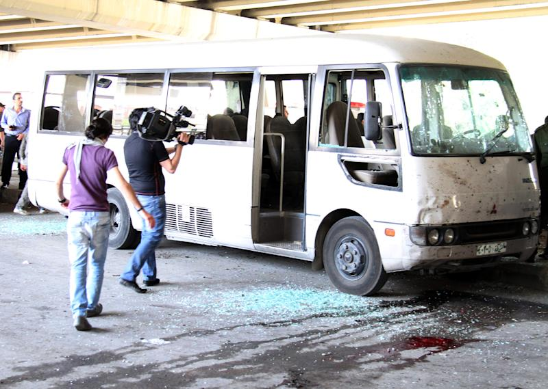 In this photo released by the Syrian official news agency SANA, a cameraman films a bus that was damaged by an explosion in the Midan neighborhood in Damascus, Syria, on Friday, April 27, 2012. A suicide bomber blew himself up across the street from a mosque in the Syrian capital Friday, killing several people and wounding 20, state TV said. Thousands of Syrians protested elsewhere to denounce persistent violence by President Bashar Assad's regime. (AP Photo/SANA)