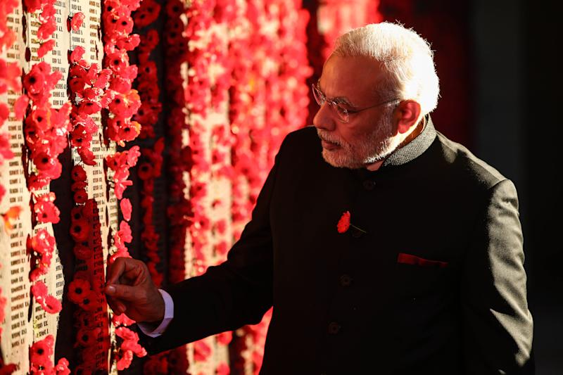 Indian Prime Minister Narendra Modi places a poppy on the wall of the Australian War Memorial, in Canberra, on November 18, 2014 (AFP Photo/Mark Nolan)
