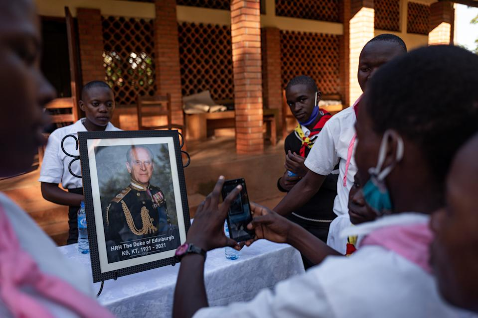 <p>Scouts and Duke of Edinburgh's Award participants take pictures of themselves with a portrait of Prince Philip Jinja, Uganda. (Getty Images)</p>