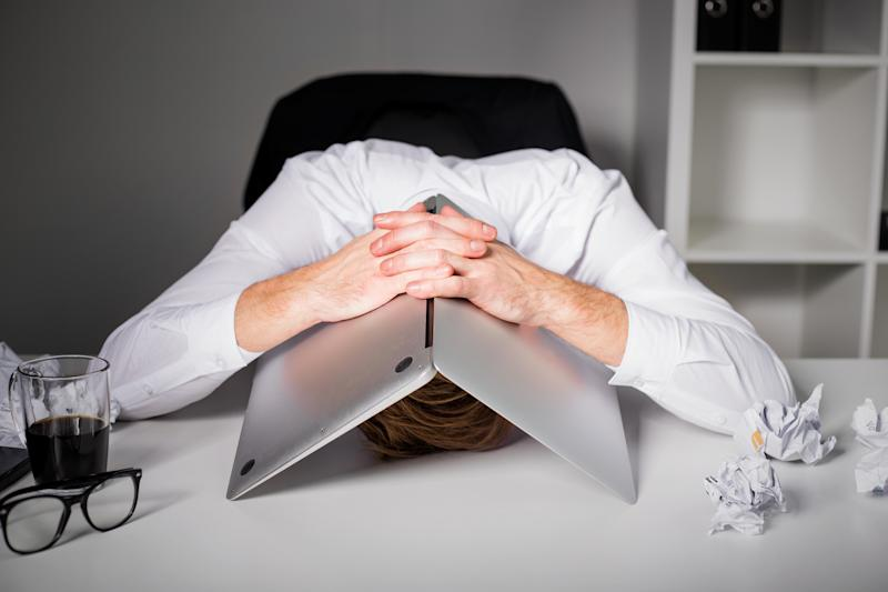 Frustrated worker with his head under his computer