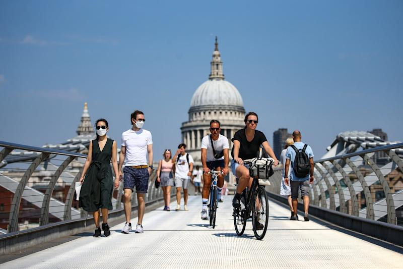 People wearing faces mask cross the Millennium Bridge: Getty Images