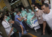 A patient is evacuated from the Bonsucesso Federal Hospital while firefighters douse a fire in Rio de Janeiro, Brazil, Tuesday, Oct. 27, 2020. According to the fire department, there were no casualties. (AP Photo/Silvia Izquierdo)