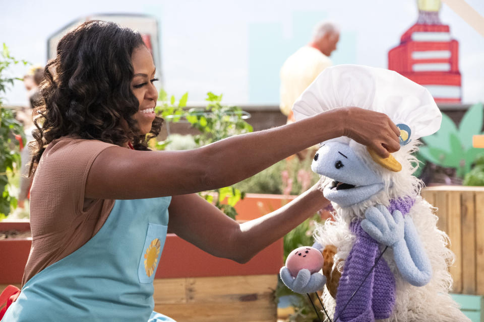 """This image released by Netflix shows former first lady Michelle Obama putting a chef's hat on Waffles, a furry puppet with waffle ears and holding Mochi, a pink round puppet, on the set of the children's series """"Waffles + Mochi."""" Obama is launching the new Netflix children's food show on March 16. (Adam Rose/Netflix via AP)"""