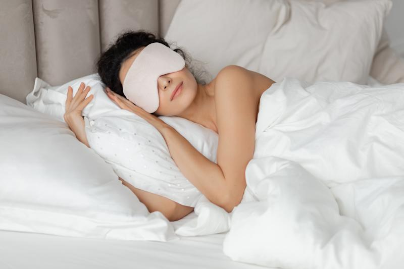 Beautiful woman sleeping seeing dreams wearing sleep mask in comfortable bed lying on soft white pillow orthopedic mattress under duvet blanket on white sheets in bedroom. Good night