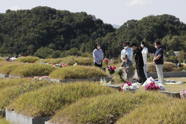 Family members wearing face masks pay respects at their ancestral cemetery ahead of Chuseok holiday, the Korean version of Thanksgiving Day, at a cemetery in Paju, South Korea, Sunday, Sept. 27, 2020. South Korea's national cemeteries will be closed during the upcoming Chuseok holiday during the five-day holidays from Sept. 30 to Oct. 4 to prevent the spread of the coronavirus. (AP Photo/Ahn Young-joon)