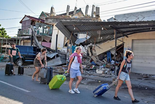 <p>Foreign tourists pull their suitcases as they walk past damaged buildings following a strong earthquake in Pemenang, North Lombok, Indonesia, Aug. 6, 2018. (Photo: Antara Foto/Ahmad Subaidi via Reuters) </p>
