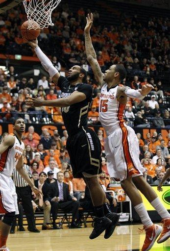 Colorado's Carlon Brown (30) lays the ball up as Oregon State's Eric Moreland (15) defends in the first half during an NCAA basketball game Saturday, March 3, 2012, in Corvallis, Ore. (AP Photo/Rick Bowmer)