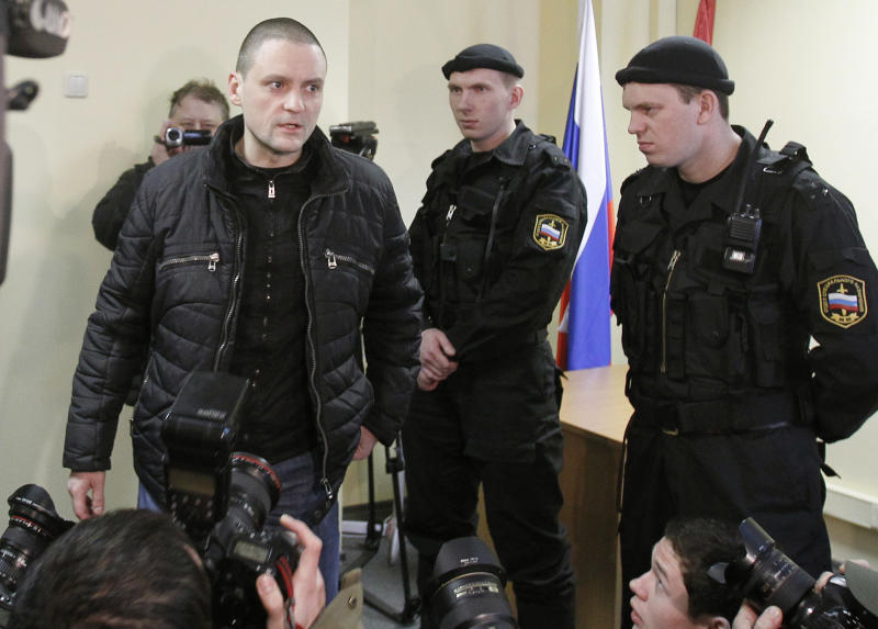 Russian opposition leader Sergei Udaltsov, left, speaks with the media at a court in Moscow, Russia, Thursday, March 15, 2012. Udaltsov was detained after Saturday's opposition rally while trying to lead his followers in a march and charged with disobeying police. (AP Photo/Misha Japaridze)