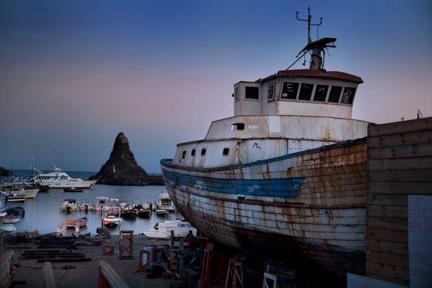 Fishing boat under repair in shipyard in Acitrezza, with famous sea stack in the background. Sicily, Italy (Photo: Busà Photography via Getty Images)