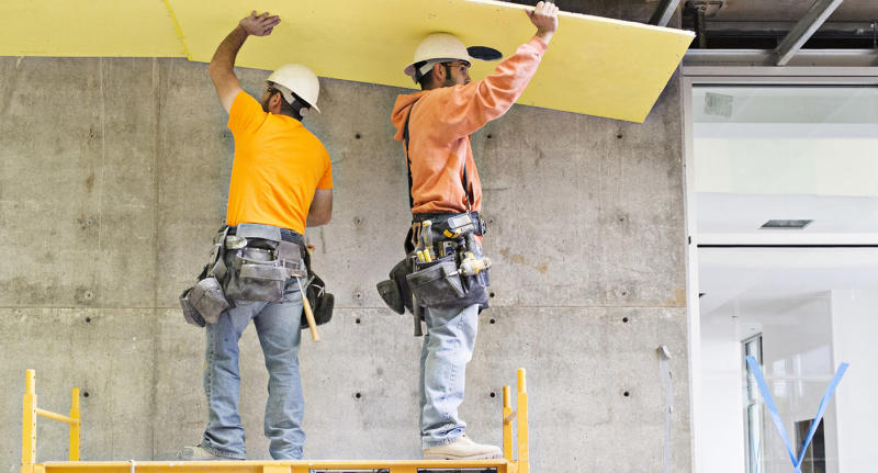 Two construction workers install insulation inside a warehouse.
