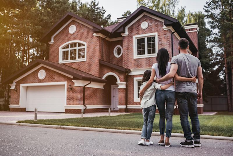A man, woman, and child stand in the street with their arms around each other and look at a house.