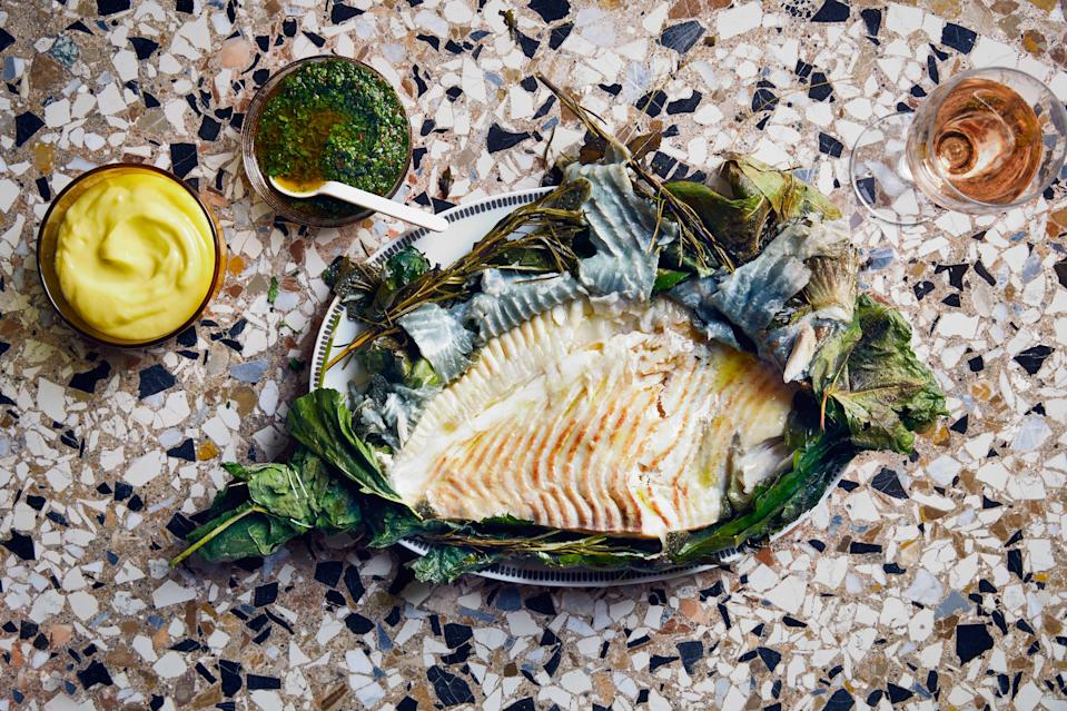 "This recipe originally called for enveloping the fish in fig leaves. They permeate the flesh, giving it a nutty flavor, and serve as both a shield to protect the flesh and a beautiful platter. But we've simplified things so you can grill the fish in a foil packet. Don't fret if you can't find turbot. Look out for other flatfish such as Dover sole or flounder. For a long, lazy lunch menu serve this fish alongside <a href=""https://www.bonappetit.com/recipe/sea-bream-crudo-with-lemon-and-olives?mbid=synd_yahoo_rss"" rel=""nofollow noopener"" target=""_blank"" data-ylk=""slk:sea bream crudo"" class=""link rapid-noclick-resp"">sea bream crudo</a>, <a href=""https://www.bonappetit.com/recipe/tomatoes-and-haricots-verts-with-anchovies?mbid=synd_yahoo_rss"" rel=""nofollow noopener"" target=""_blank"" data-ylk=""slk:tomatoes and haricots verts"" class=""link rapid-noclick-resp"">tomatoes and haricots verts</a>, <a href=""https://www.bonappetit.com/recipe/malfatti-with-pancetta-and-cherry-tomatoes?mbid=synd_yahoo_rss"" rel=""nofollow noopener"" target=""_blank"" data-ylk=""slk:handmade malfatti"" class=""link rapid-noclick-resp"">handmade malfatti</a>, and <a href=""http://bonappetit.com/recipe/tiramisu-with-amaretti-cookies"" rel=""nofollow noopener"" target=""_blank"" data-ylk=""slk:tiramisù with cookies."" class=""link rapid-noclick-resp"">tiramisù with cookies.</a> <a href=""https://www.bonappetit.com/recipe/grilled-turbot-with-celery-leaf-salsa-verde?mbid=synd_yahoo_rss"" rel=""nofollow noopener"" target=""_blank"" data-ylk=""slk:See recipe."" class=""link rapid-noclick-resp"">See recipe.</a>"