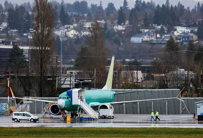 Employees walk near a Boeing 737 Max aircraft at the Renton Municipal Airport in Renton
