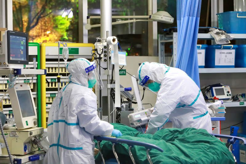 Medical staff in protective suits treat a patient with pneumonia caused by the new coronavirus at the Zhongnan Hospital of Wuhan University, in Wuhan