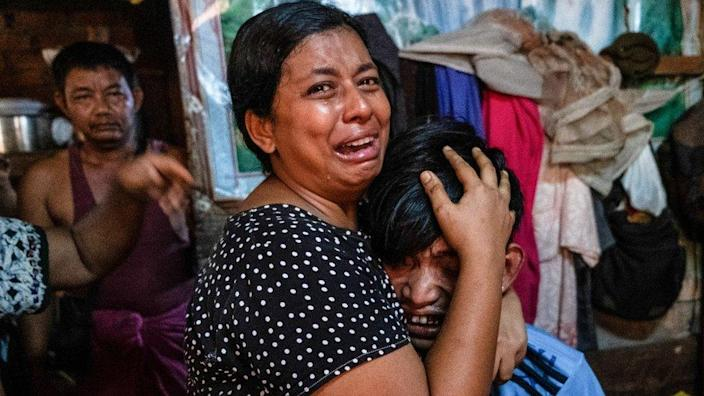 Family members cry in front of a man after he was shot dead during an anti-coup protesters crackdown in Yangon, Myanmar, March 27, 2021.