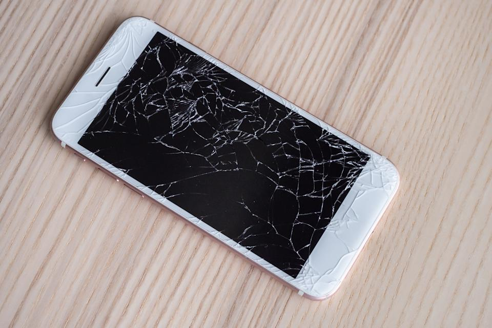 broken glass of mobile phone screen on wooden background