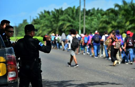 Guatemalan policemen film Honduran migrants heading north after they broke through the country's southern border with Honduras