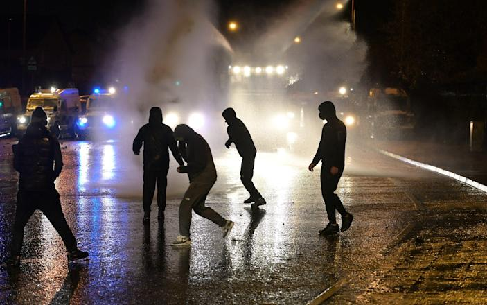 Nationalists attack police vehicles as they deploy water canons on Springfield Road just up from Peace Wall interface gates which divide the nationalist and loyalist communities on April 8, 2021 in Belfast - Charles McQuillan/Getty