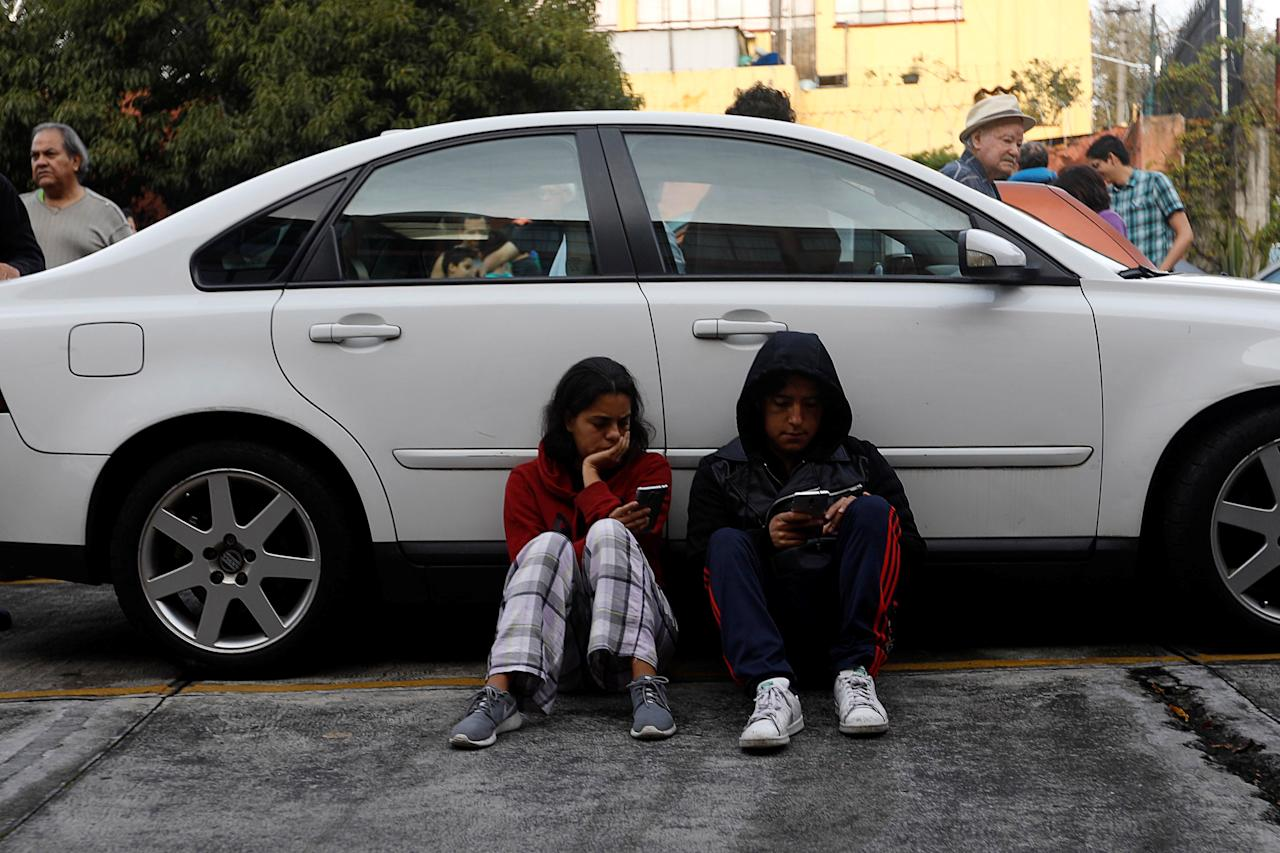 A couple sits beside a car inside a residential area after a tremor was felt in Mexico City, Mexico, September 23, 2017. REUTERS/Edgard Garrido