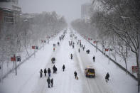 "People walk along ""El Paseo de la Castellana"" avenue during a heavy snowfall in Madrid, Spain, Saturday, Jan. 9, 2021. A persistent blizzard has blanketed large parts of Spain with 50-year record levels of snow, halting traffic and leaving thousands trapped in cars or in train stations and airports that suspended all services as the snow kept falling on Saturday. (AP Photo/Andrea Comas)"