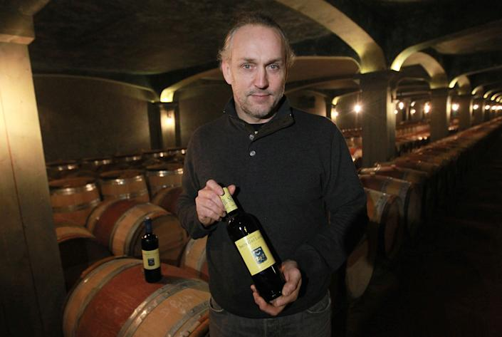 In this photo dated Wednesday, Nov. 13, 2013, Fabien Teitgen, head of the wine making holds a bottle of red wine of Chateau Smith Haut Lafitte in the wine cellars of Chateau Smith Haut Lafitte in Martillac, near Bordeaux,bsouthwestern France. Counterfeiting has dogged wine as long as it has been produced, but it is getting more sophisticated and more ambitious, particularly as bottle prices rise due to huge demand in new markets, mainly in Asia. (AP Photo/Bob Edme)