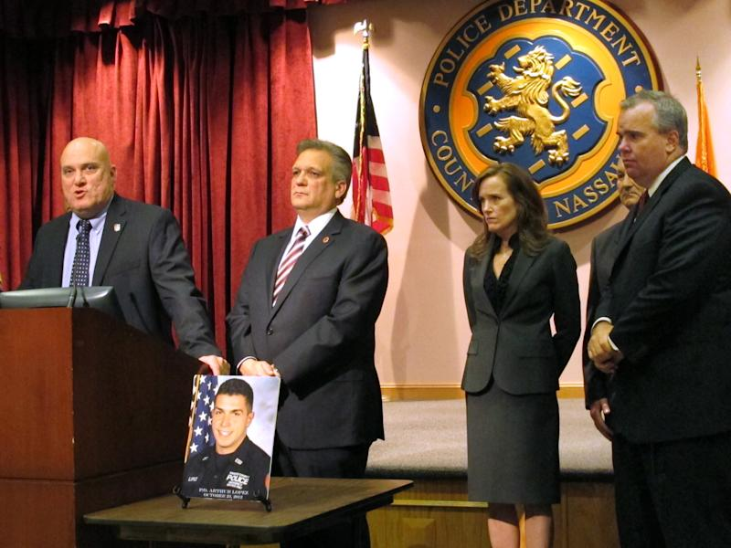 Nassau County PBA President James Carver, left, discusses the shooting death of Police Officer Arthur Lopez, shown in picture on table, at a news conference, Tuesday, Oct. 24, 2012 at Police Headquarters in Mineola, N.Y. Listening from second left are Nassau County Executive Edward Mangano, District Attorney Kathleen Rice, County Comptroller George Maragos and First Deputy Police Commissioner Thomas Krumpter. A motorist fleeing a possible hit-and-run traffic accident fatally shot Lopez in broad daylight Tuesday near the Belmont racetrack and then apparently killed another driver not far away during a carjacking, authorities said. (AP Photo/Frank Eltman)