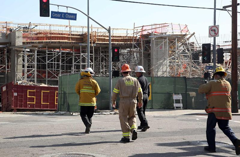 Los Angeles Firefighters arrive at the site of a parking structure under construction that collapsed Friday March 28, 2014 in Los Angeles. A section of the parking structure under collapsed, but authorities say it appears no one was hurt. (AP Photo/Nick Ut)