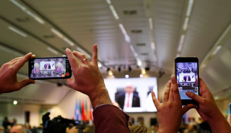 Journalists take pictures at the beginning of an OPEC and NON-OPEC meeting in Vienna