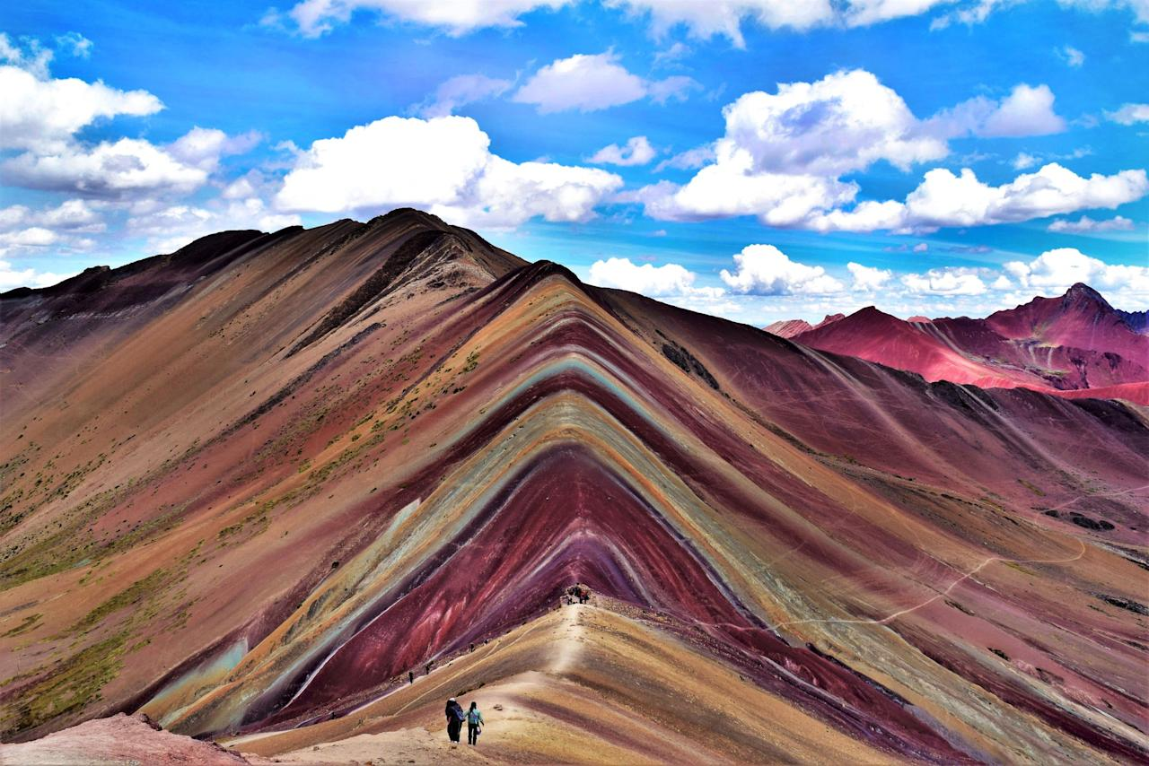 <p>Hikers climb the side of a rainbow-striped mountain in Peru. (Tristan Oliff/Caters News) </p>