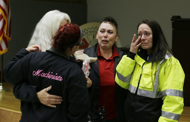 Boeing workers cry after learning that voters in District 751 of the Boeing machinists union voted to accept Boeing's latest contract offer to keep the assembly of the Boeing 777X airplane in Washington state, Friday, Jan. 3, 2014, in Seattle. (AP Photo/Ted S. Warren)