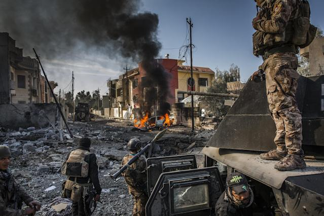 <p>The battle for Mosul: Iraqi Special Forces soldiers survey the aftermath of an attack by an ISIS suicide car bomber, who managed to reach their lines in the Andalus neighborhood, one of the last areas to be liberated in eastern Mosul, Jan. 16, 2017.<br><br>On July 10, 2017, after months of fighting, the Iraqi government declared the city of Mosul fully liberated from ISIS, although fierce fighting continued in pockets of the city. Mosul had fallen to ISIS three years earlier, and the battle to retake it had begun in Oct. 2016.<br>In effect, the reconquering of Mosul comprised two parts: the battle for the eastern half of the city, and that for the west, across the Tigris River. East Mosul was recaptured by the end of Jan. 2017, but the offensive on west Mosul, particularly the densely built-up Old City, proved more difficult. Large areas of the city were left in ruins, and huge numbers of civilians were caught in the crossfire as battle raged.<br>A United Nations report gives an absolute minimum of 4,194 civilian casualties during the conflict, with other sources putting the figure much higher. The Office of the UN High Commissioner for Human Rights pointed to extensive use of civilians as human shields, with ISIS fighters attempting to use the presence of civilian hostages to make certain areas immune from military operations.<br>After months of being trapped in the last remaining ISIS-held areas of the city, the people in west Mosul were severely short of food and water. Those who chose to remain in the city rather than go to one of the many camps for displaced people, initially relied on aid in order to survive. (Photo: Ivor Prickett for The New York Times) </p>