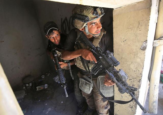 <p>Members of the Iraqi anti-terrorism forces (CTS) look on from behind a wall in the Old City of Mosul on June 22, 2017, during the ongoing offensive by Iraqi forces to retake the last district still held by the Islamic State (IS) group. (Photo: Ahmad al-Rubaye/AFP/Getty Images) </p>