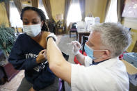 Walgreens pharmacist Chris McLaurin prepares to vaccinate Lakandra McNealy, a Harmony Court Assisted Living employee, with the Pfizer-BioNTech COVID-19 vaccine, Tuesday, Jan. 12, 2021, in Jackson, Miss. The Mississippi State Department of Health reports there have been 9,796 cases of the coronavirus in long-term care facilities and 1,791 deaths as of Tuesday. (AP Photo/Rogelio V. Solis)