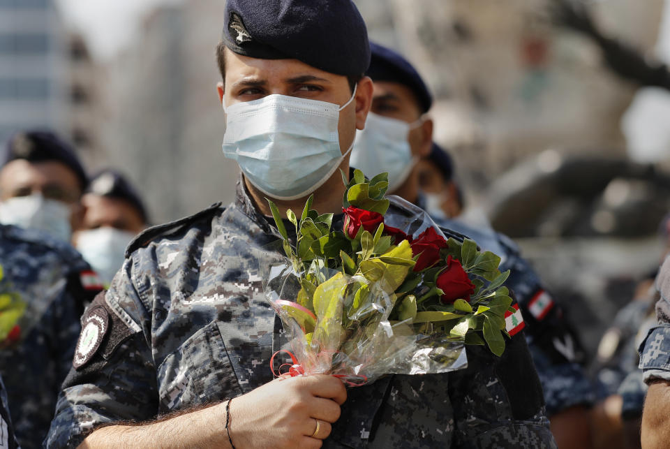 Police hold flowers to mark the first anniversary of Beirut's massive 2020 seaport blast in Beirut, Lebanon, Wednesday, Aug. 4, 2021. Lebanon is marking one year since the horrific explosion at Beirut port. The grim anniversary Wednesday comes amid an unprecedented economic and financial meltdown and a political stalemate that has kept the country without a functioning government for a full year. (AP Photo/Hussein Malla)