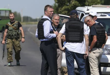 Hug, deputy head for the OSCE monitoring mission in Ukraine, stands with members of his team on the way to the site where the downed Malaysian airliner MH17 crashed, outside Donetsk