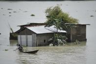 A man uses a boat to move across a flooded area in a flood effected village in Morigaon district of Assam in India on Friday, 17 July 2020. (Photo by David Talukdar/NurPhoto via Getty Images)