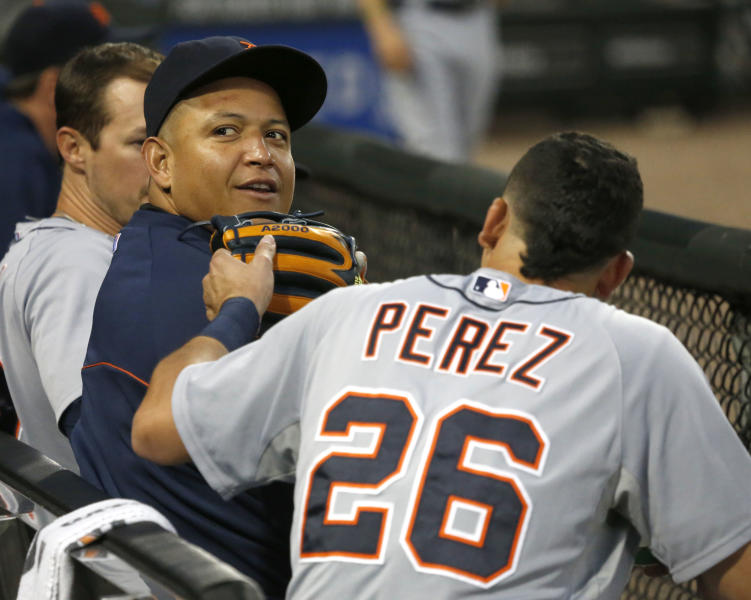 Detroit Tigers' Miguel Cabrera, left, looks up into the stadium as he sits in the dugout with shortstop Hernan Perez during the fifth inning of a baseball game against the Chicago White Sox on Wednesday, July 24, 2013, in Chicago. (AP Photo/Charles Rex Arbogast)
