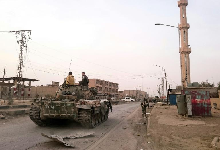 Members of the pro-Syrian government forces ride on a tank as it drives down a street in the Syrian border town of Albu Kamal