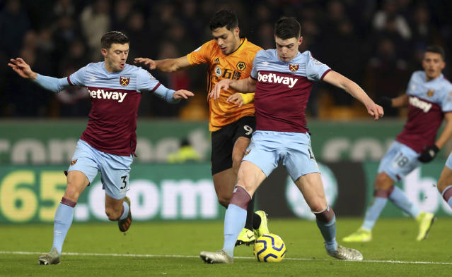 Wolverhampton Wanderers's Raul Jimenez, centre, challenges with West Ham United's Declan Rice, right, and Aaron Cresswell during their English Premier League soccer match at Molineux in Wolverhampton, England, Wednesday Dec. 4, 2019. (David Davies/PA via AP)