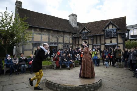 Tourists watch actors perform at the house where William Shakespeare was born during celebrations to mark the 400th anniversary of the playwright's death in Stratford-Upon-Avon, Britain, April 23, 2016. REUTERS/Dylan Martinez/File Photo