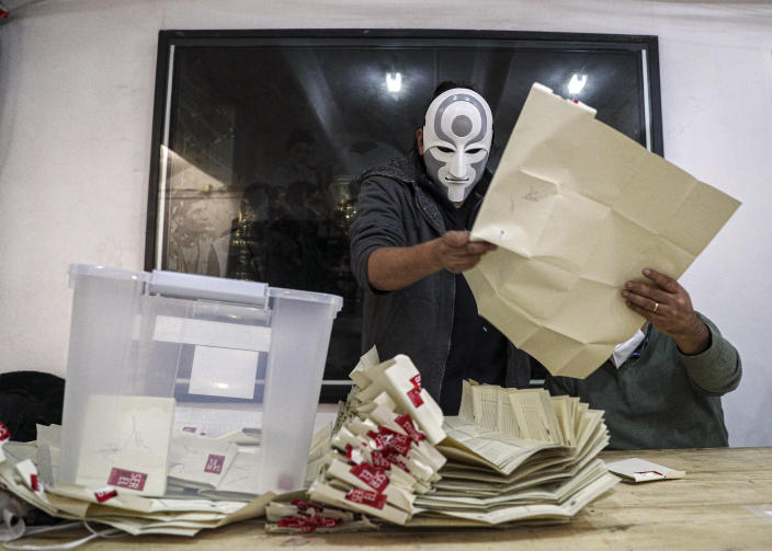 An electoral worker with a mask of the Amon character of the Legend of Korra animated series counts ballots after the second day of the Constitutional Convention election to select assembly members that will draft a new constitution, in Santiago, Chile, Sunday, May 16, 2021. The South American country is choosing 155 people to draft a constitution to replace one that has governed it since being imposed during a military dictatorship. (AP Photo/Esteban Felix)