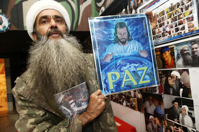 SAO PAULO, BRAZIL - APRIL 29: Osama bin Laden lookalike Ceara Francisco Helder Braga Fernandes poses with a portrait of Jesus in his 'Bar do Bin Laden' on April 29, 2014 in Sao Paulo, Brazil. Braga says he was known as the 'Beard Man' before 9/11 but became known as a Bin Laden lookalike following the 9/11 attacks. He says he is Christian and continues to play the role to support his business. (Photo by Mario Tama/Getty Images)