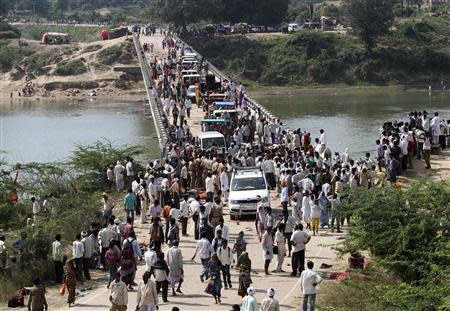 People cross a bridge after a stampede near Ratangarh temple in Datia