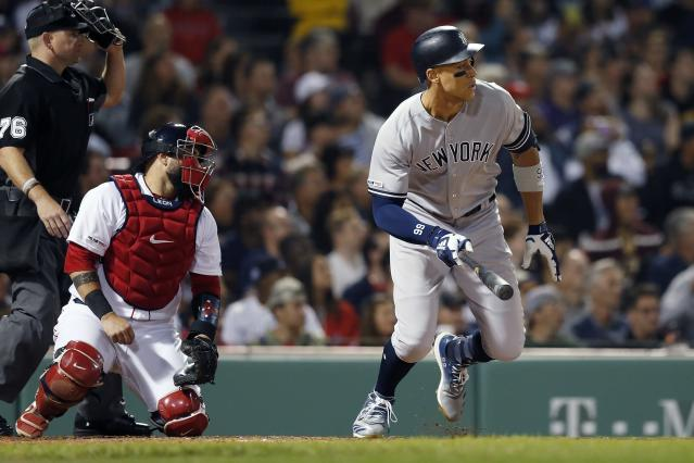 New York Yankees' Aaron Judge, right, watches his RBI-single in front of Boston Red Sox's Sandy Leon during the third inning of a baseball game in Boston, Sunday, Sept. 8, 2019. (AP Photo/Michael Dwyer)