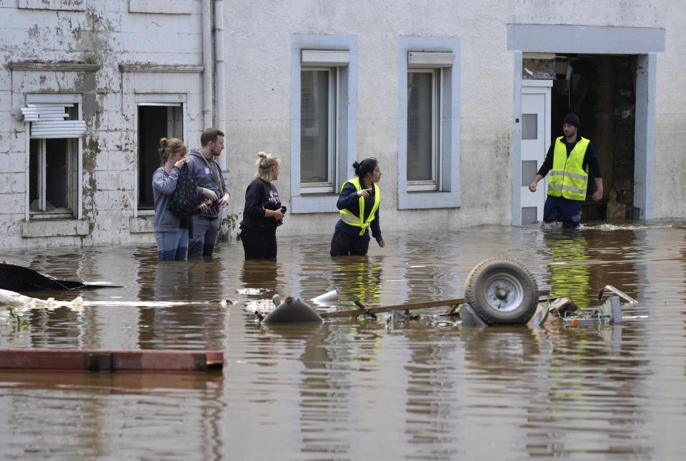 People walk in floodwaters in Pepinster, Belgium, Saturday, July 17, 2021. Residents in several provinces were cleaning up after severe flooding in Germany and Belgium turned streams and streets into raging torrents that swept away cars and caused houses to collapse. (AP Photo/Virginia Mayo)
