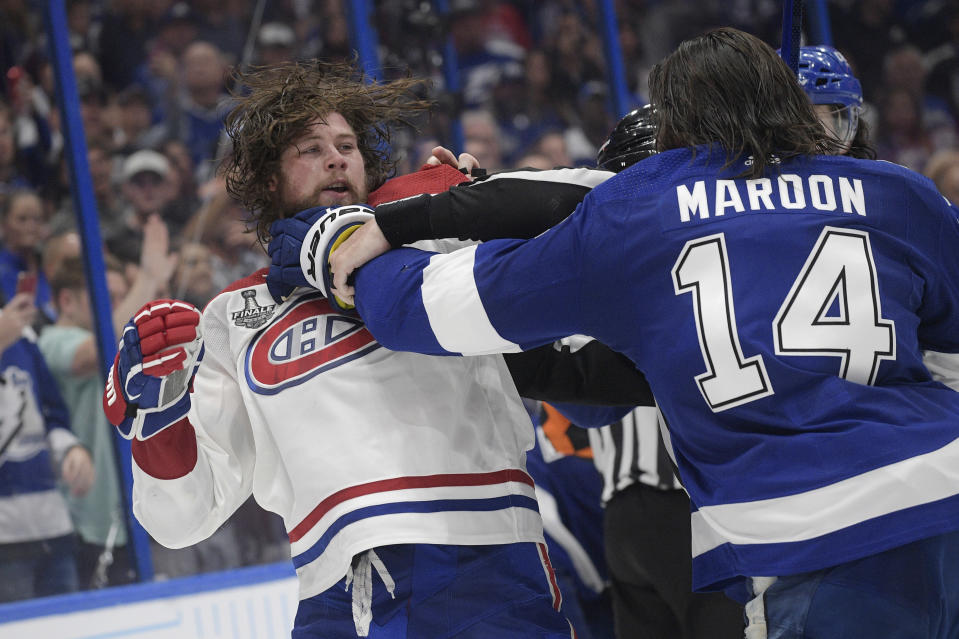 A referee breaks up Montreal Canadiens right wing Josh Anderson, left, and Tampa Bay Lightning left wing Pat Maroon (14) during the third period in Game 1 of the NHL hockey Stanley Cup finals, Monday, June 28, 2021, in Tampa, Fla. (AP Photo/Phelan Ebenhack)
