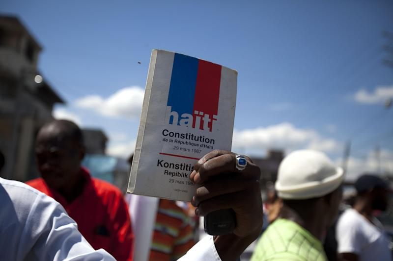 A supporter of two-time President Jean-Bertrand Aristide holds up a copy of Haiti's Constitution during a demonstration marking the 27th anniversary of the signing of Constitution, in Port-au-Prince, Haiti, Saturday, March 29, 2014. Those demonstrating called for the resignation of President Michel Martelly. The protesters say Martelly hasn't done enough to alleviate hunger since he was sworn in as president in May 2011. ( AP Photo/Dieu Nalio Chery)